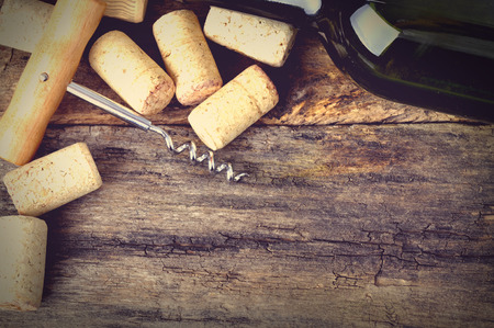 brown cork: Bottle of white wine, corkscrew and corks on wooden table. Background Stock Photo