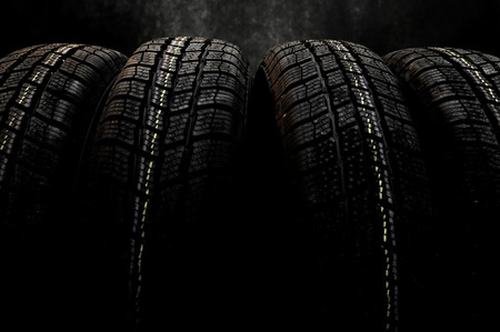 winter tires: Dark background with winter tires Stock Photo