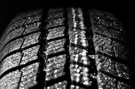 Winter car tire in rain, dark background photo