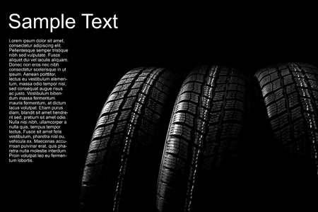 winter tires: Dark background with winter car tires Stock Photo