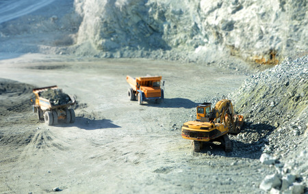 construction machines: Big yellow trucks in quarry with tilt-shift effect