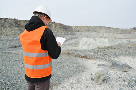 Worker in a helmet and quarry in background Imagens