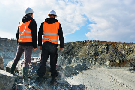 job site: Two workers and quarry in background Stock Photo