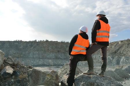 mining: Two workers and quarry in background Stock Photo
