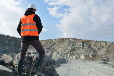 hard: Worker in a helmet and quarry in background Stock Photo