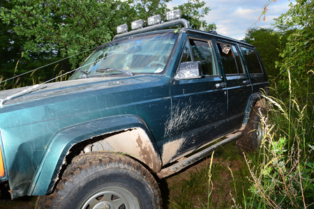 muddy tracks: 4x4 offroad truck in forest.