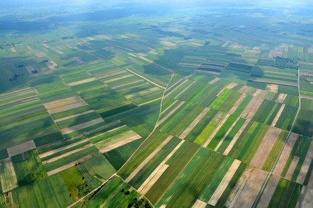 aerial views: Aerial view of the countryside with village and fields of crops in summer