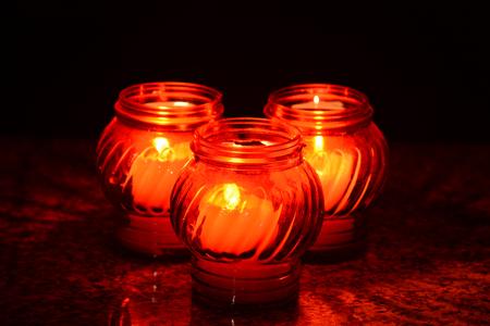 candela: Candele che brucia in un cimitero durante la festa di Ognissanti. Profondità di campo.