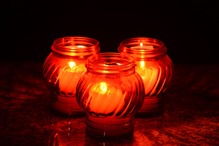 during the day: Candles Burning At a Cemetery During All Saints Day. Shallow depth of field. Stock Photo
