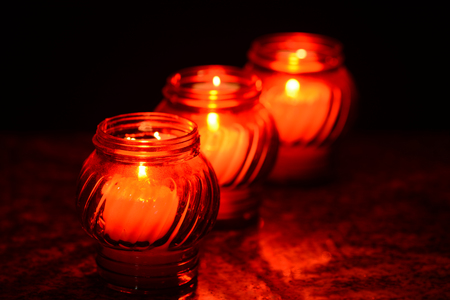 hallowmas: Candles Burning At a Cemetery During All Saints Day. Shallow depth of field. Stock Photo