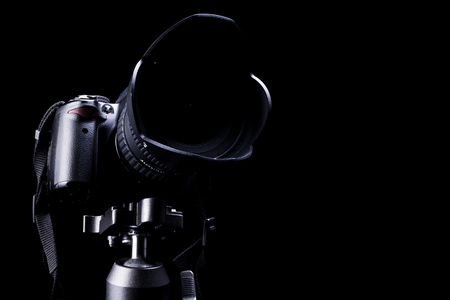 photojournalist: Professional DSLR camera on black  background.