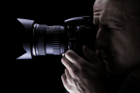 Young professional photographer taking pictures with digital camera Imagens