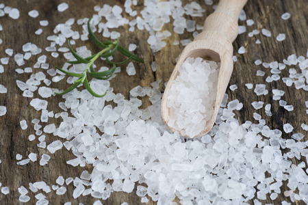 salt crystal: Closeup of sea salt on wooden table