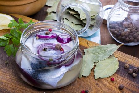 Gemarineerde haring in een potje met kruiden Stockfoto