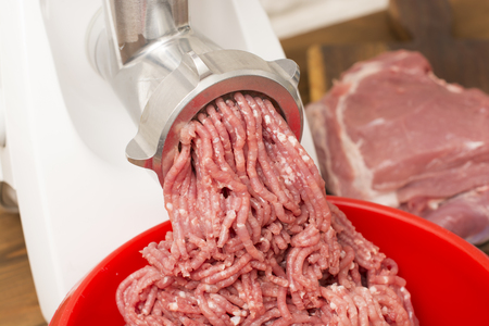 food processing: Closeup of minced meat coming out from grinder. Healthy homemade minced meat