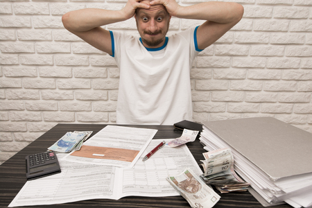 form: Stressed man during filling Tax Forms