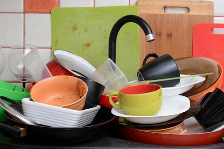 habitacion desordenada: Pila de platos sucios en el fregadero de