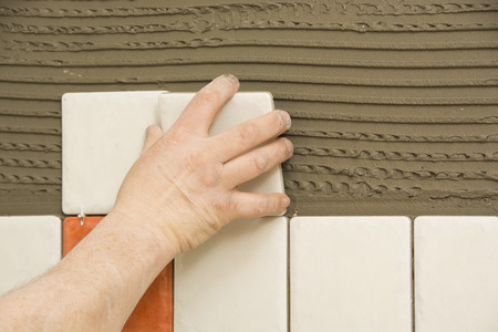 tile adhesive: Man installing ceramic tile on a wall