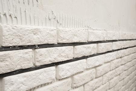 Installing white decorative bricks on the wall