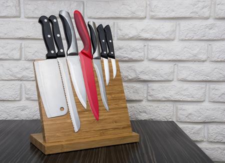 Set of knives on wooden magnetic holder