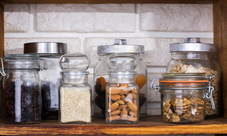 Jars with dried fruits and nuts on shelf