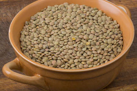 lenteja: Lentil in bowl on wooden table