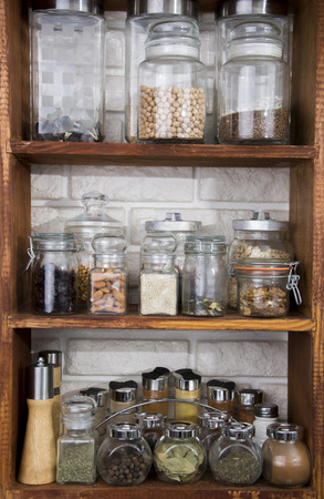 Jars with nuts, dried fruits, spices, herbs and others on kitchen shelves Zdjęcie Seryjne