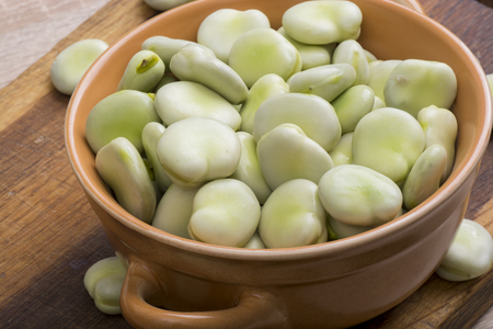 Fresh broad beans in bowl on wooden board Zdjęcie Seryjne