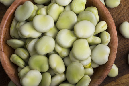 Fresh broad beans in bowl on wooden board Stock Photo
