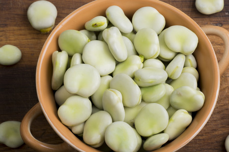 broad: Fresh broad beans in bowl on wooden board Stock Photo