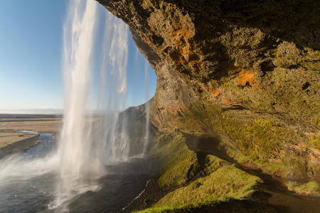 A view of famous Seljalandsfoss waterfall from behind the fall , Iceland photo
