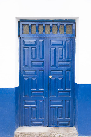A blue antique door with great design with white wall