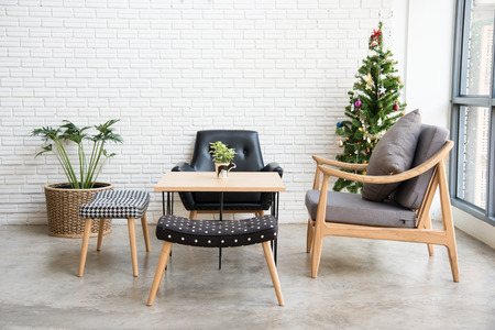 dining table and chairs: cozy sofa corner with christmas tree decoration at the back. sofa is in modern style and made with wood. Stock Photo