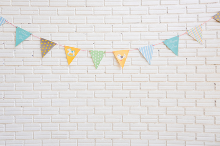 happy people white background: A white brick wall decorated by colorful cartoon flag for children bedroom, play space or living room Stock Photo
