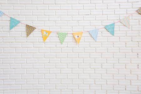 garderie: Un mur de briques blanches décoré par drapeau coloré de bande dessinée pour les enfants chambre, jouer l'espace ou le salon