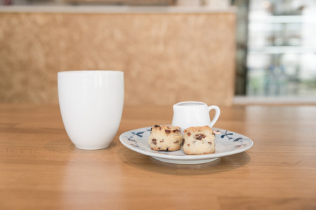scone: coffee cup and scone in cafe in retro style.