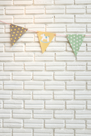 White brick wall decorated by colorful cartoon flag for children for children's room or babyshower party Reklamní fotografie