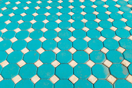 Footpath made by square blue tiles with illusional perspective