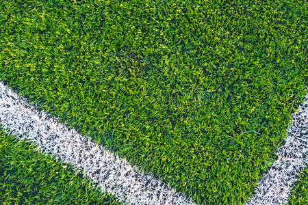 A top down angle view of white line on a green soccer field.
