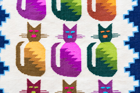 Close up peruvian fabric souvenir's of colorful cats pattern.  The souvenir is handmade with colorful dyed wool. Reklamní fotografie