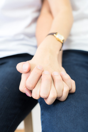 Close up a couple wearing white shirts and dark blue jeans holding hands tightly