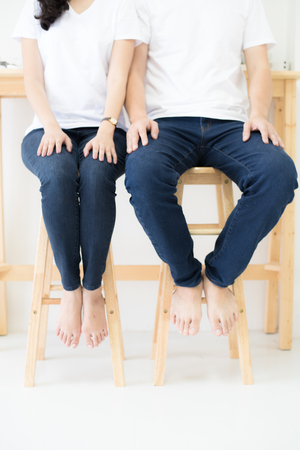 Couple wearings white shirt and blue jeans sitting on wood chairs