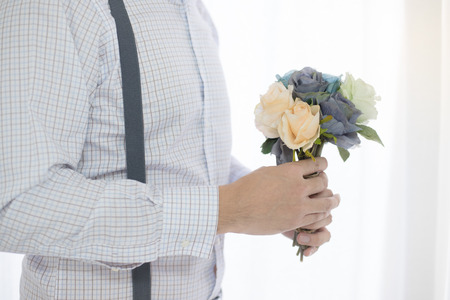 Close up man holding flower bouquet by window