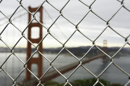 View of Golden Gate bridge from top view in foggy day through fence