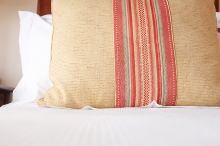 pillow with luxurious, elegant design placing on a wooden bed covered with white sheet Reklamní fotografie