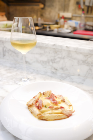 Pasta with bacon in cream sauce serving with white wine on a white marble table near the open kitchen. The dish is decorated in dedicated, fine dining style