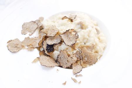 Risotto gekookt met witte rijst op de top met zwart gesneden truffel op een witte plek.