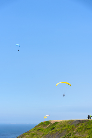 tourists paragliding in the sky over the ocean coast
