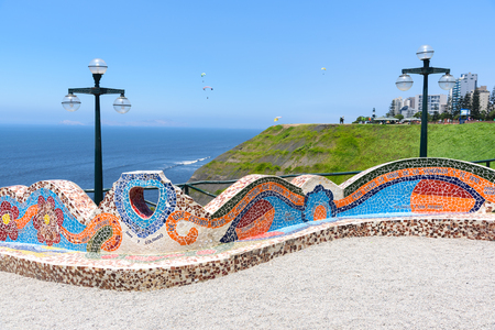 Colorful chairs in the park made with mosaic stones. The background is the shore and blue sky.
