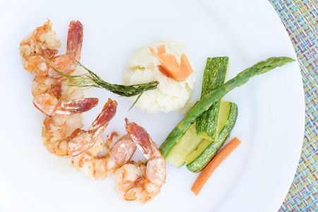 grilled shrimps or shrimps skewer on plate with green salad